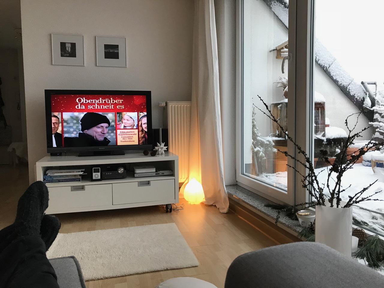 """Blick auf den TV mit dem Film """"Obendrüber das schneit es"""" und Blick auf die verschneite Terrasse"""