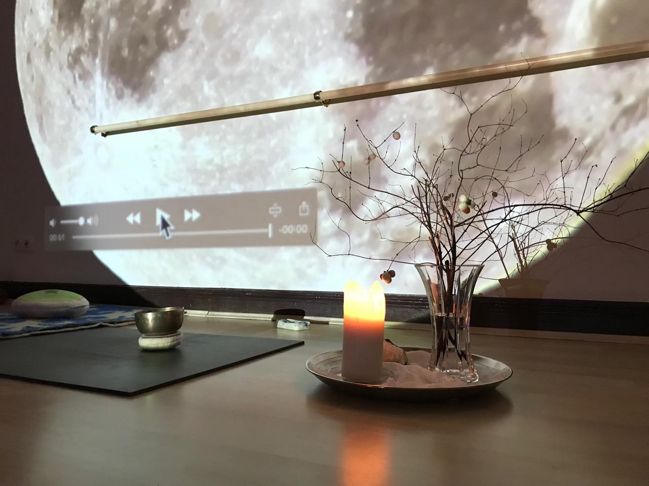 Yoga Vollmond: Ein Tabeltt mit einer Vase voll Zweigen und eine Kerze vor einem Mond-Foto