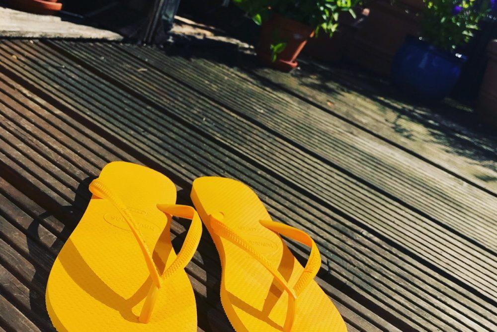 Gelbe Flips Flops auf der Terrasse