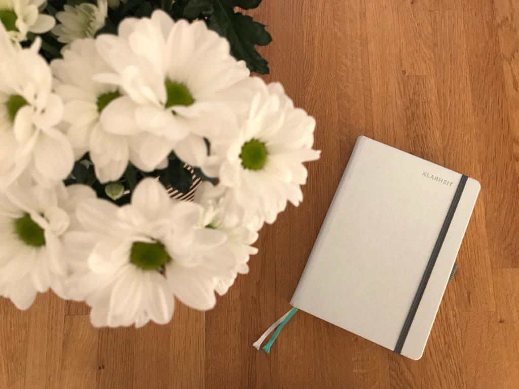 Papierkalender: Klarheit neben Blumen