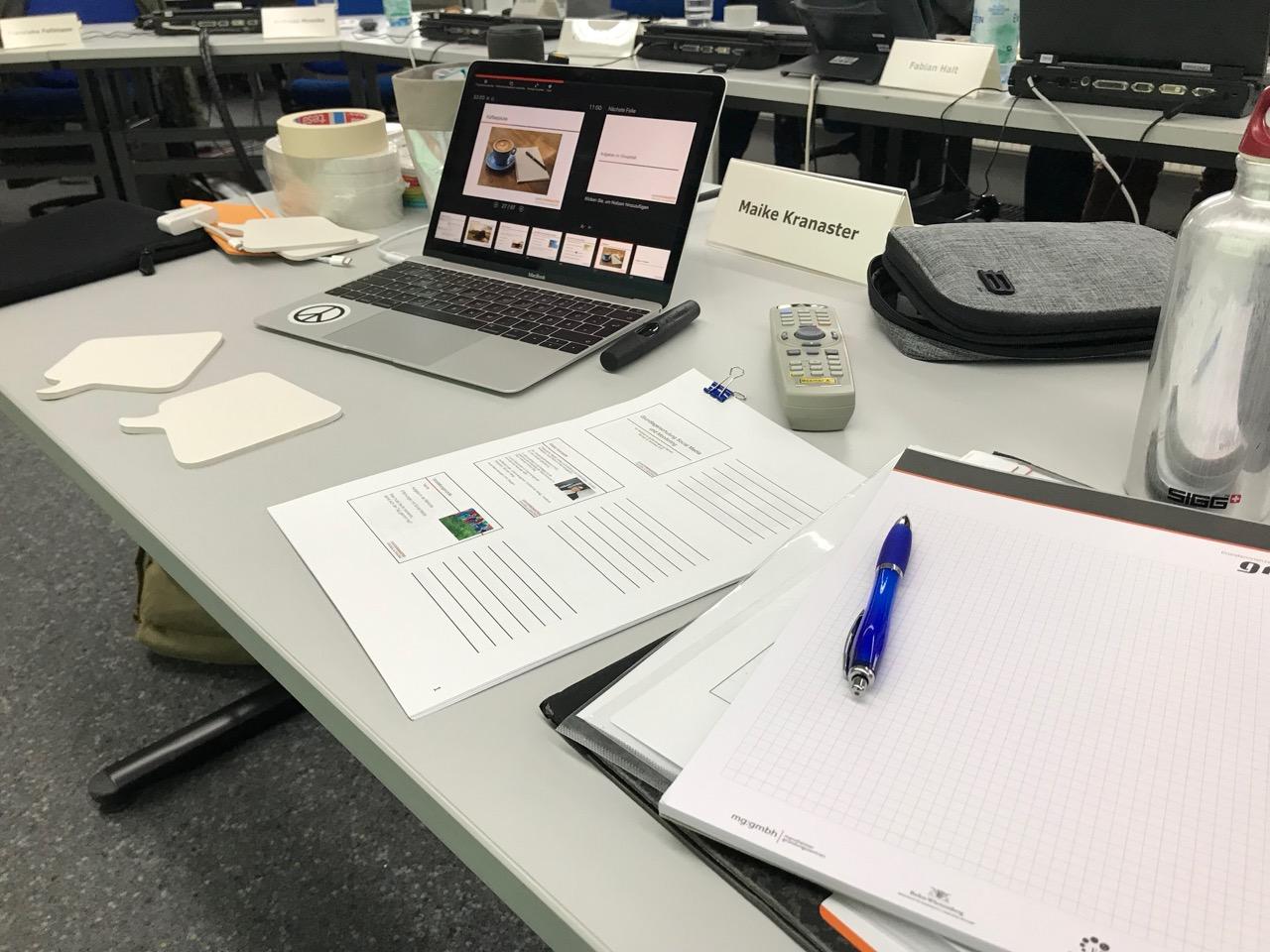 Seminar: Tisch mit Laptop, Namensschild und Unterlagen