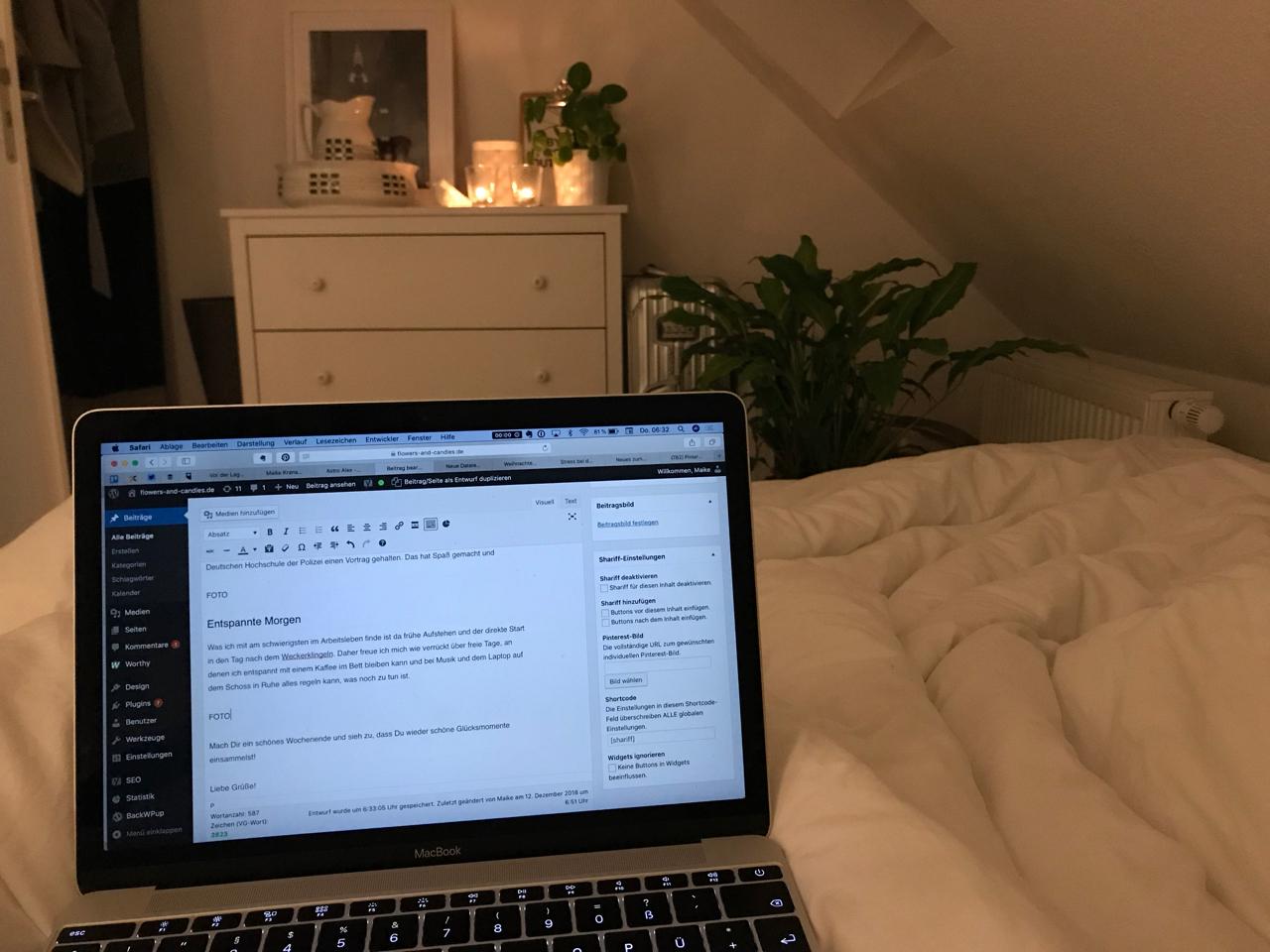 Kaffee im Bett: Laptop auf dem Schoss, im Hintergrund brennen Kerzen