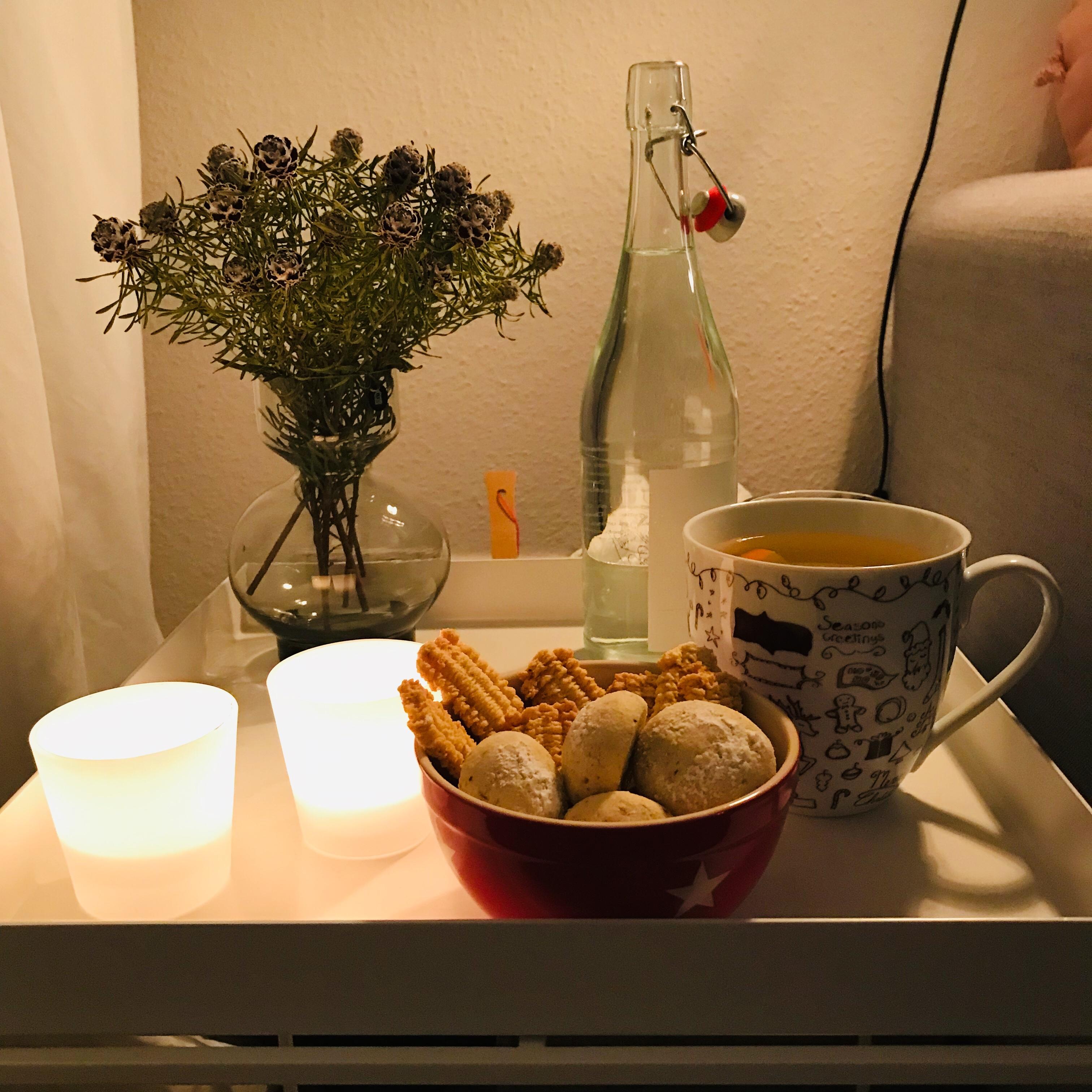 Kekse auf dem Tisch mit Kerzen und Tee