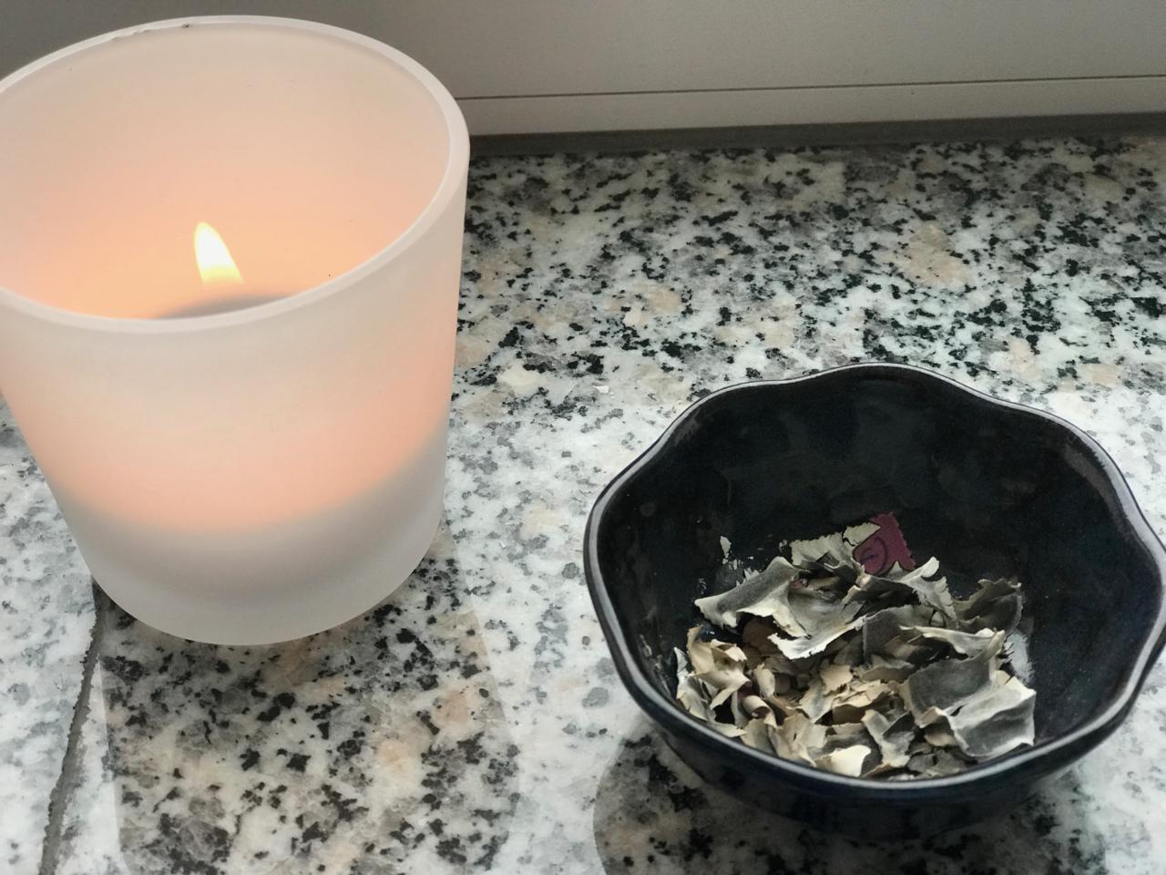 Wünscheritual: Kerze und ein Schälchen mit Asche daneben