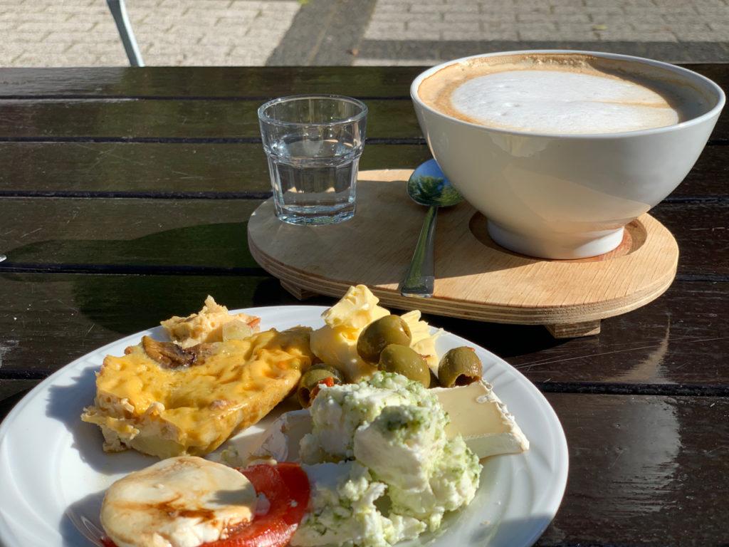 Frühstück im Seitenblick: Milchkaffee mit einem bunten Teller