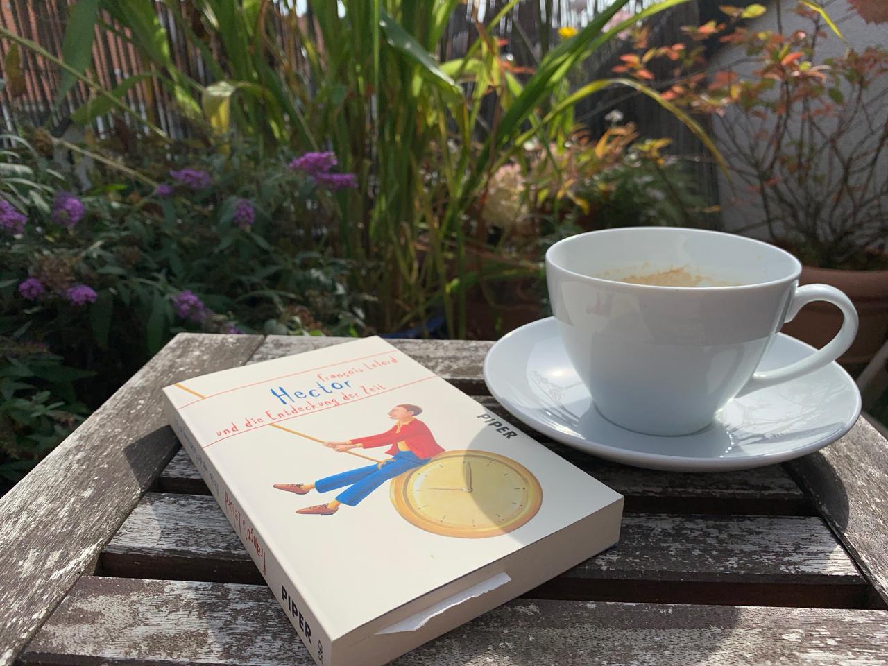 Sommertag auf der Terrasse mit Buch und Kaffee