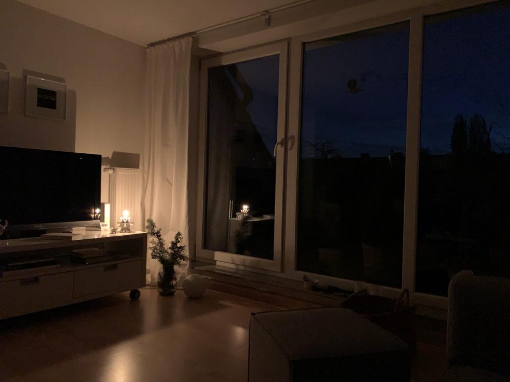 Auf den Sonnenaufgang warten: Dunkles Wohnimmer, nur von einer Kerze beleuchtet