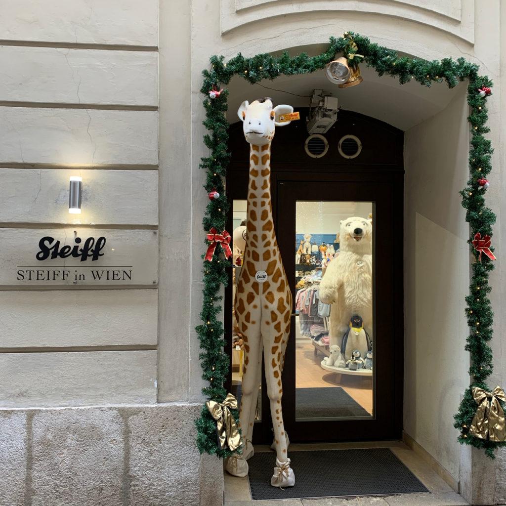 Schaufenster Wien zur Weihnachtszeit: Steiff-Geschäft mit etwa 2 Meter großer Giraffe von Steiff im Eingang