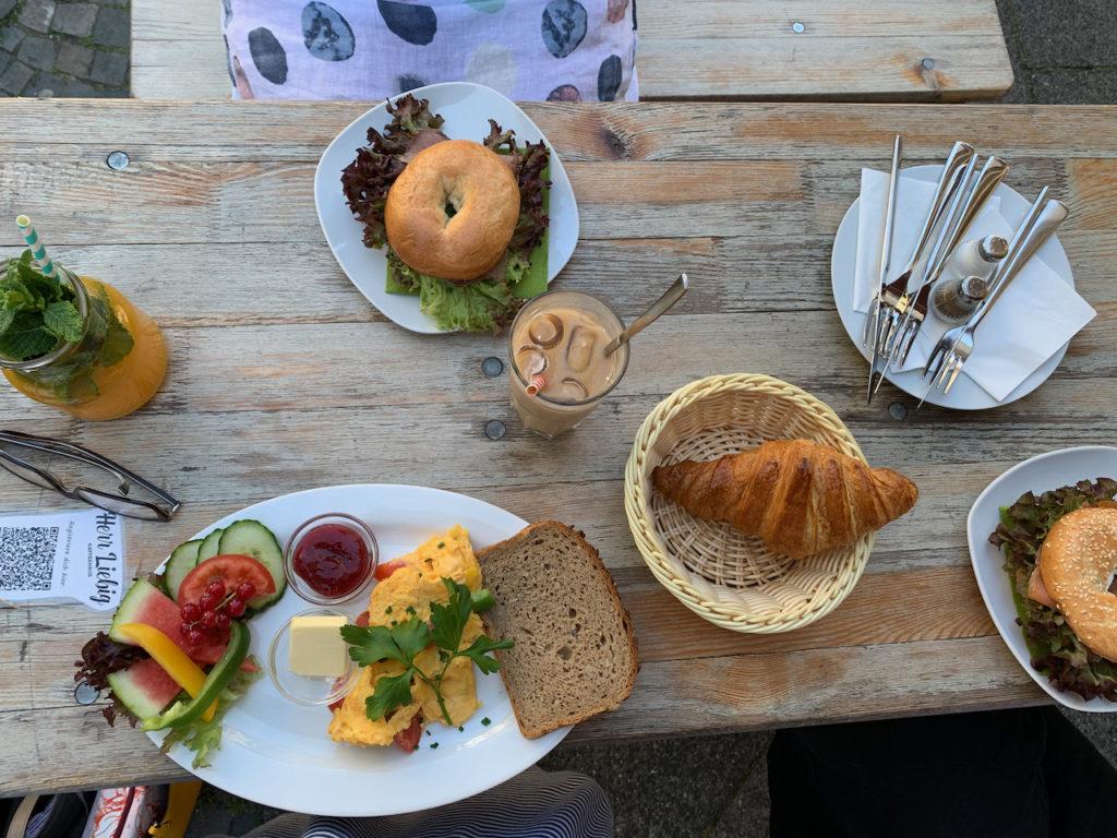 Frühstück bei Herrn Liebig: Tisch mit Bagels, Rührei, Croissant und Getränken