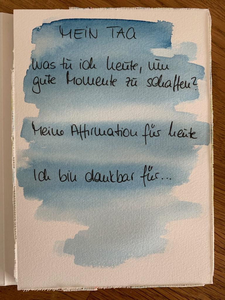 Aquarellpapier mit Text, hinterlegt mit blauer Aquarellfarbe. Hier steht: Mein Tag, Was tu ich heute, um gute Momente zu schaffen?, Meine Affirmation für heute, Ich bin dankbar für...