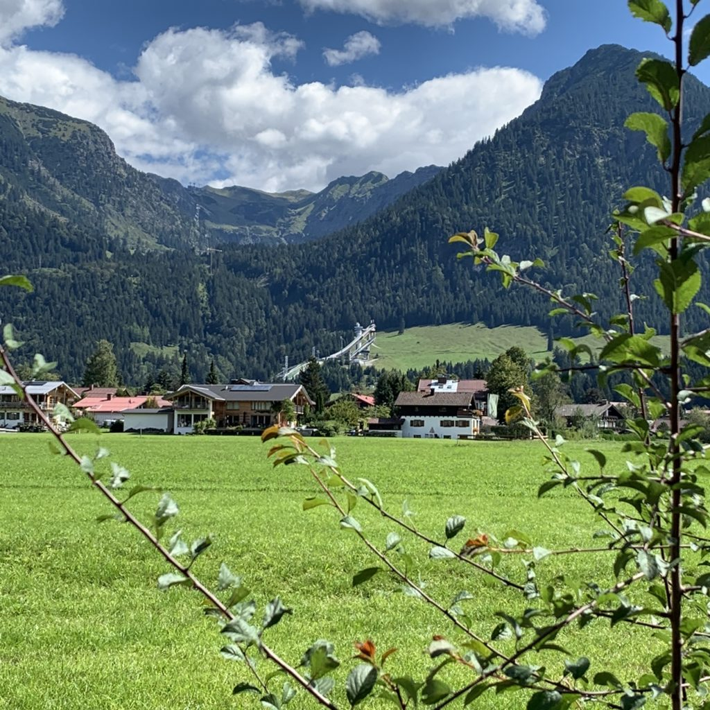 Oberstdorf: Blick über die große Wiese über Oberstdorf mit Skisprungschanze und Nebelhorn im Hintergrund